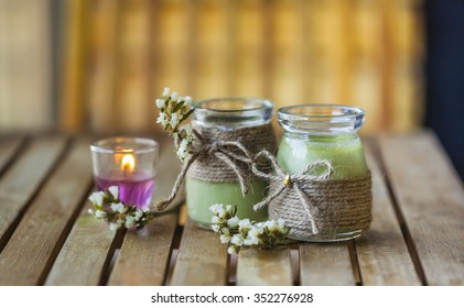 Green tea cakes in jars with candle, flowers on wooden background.