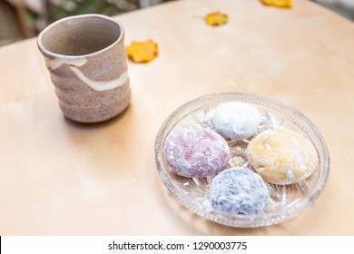 Green tea ceramic cup and mochi rice cake Japanese dessert wagashi colorful daifuku pieces on autumn season leaves on table color
