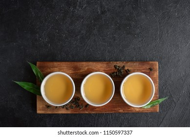 Green tea in ceramic cups, dry green oolong tea and tea leaves on black stone table, top view, copy space.