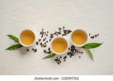 Green tea in ceramic cups, dry green oolong tea and tea leaves on white stone table, top view, copy space.