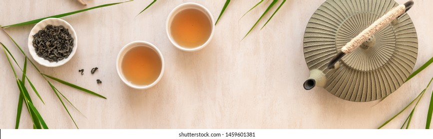 Green Tea Composition with bamboo leaves, banner. Chinese traditional tea set, tea ceremony concept, top view, copy space.