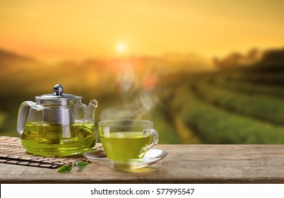 Green tea cup and glass jars with fresh green tea leaves on the wooden table and the tea plantations background with copy space
