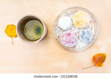 Green tea cup and mochi rice cake Japanese dessert wagashi colorful daifuku autumn leaves on table color and flat top view