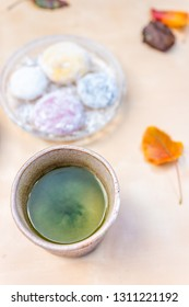 Green tea cup and mochi rice cake Japanese dessert wagashi colorful daifuku autumn season leaves on table color and vertical flat top view
