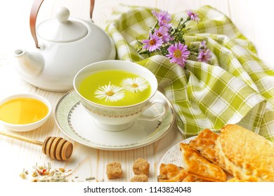 Green tea in a cup on a background of dry leaves of floral tea in a composition with accessories on a white background
