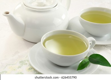 Green tea cup and tea pot isolated on white background
