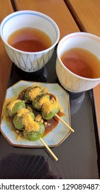 Green tea Dango dessert with with Brown Sugar Syrup and Kinako ( Roasted Soy Flour ) serve on plate with ho tea.
