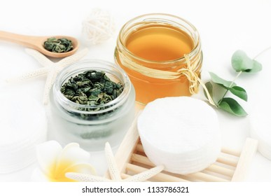 Green tea exract homemade facial tonic refreshing skin care. Glass jars of tea leaves and tincture prepared on white table.