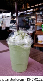 Green tea frappe with whip cream on table