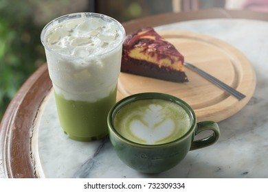 Green tea frappucino in takeaway cup and cheesecake on the marble background.