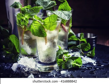 Green tea with ice, mint and white rum, dark background, selective focus