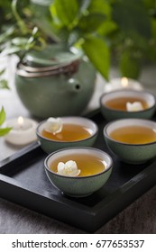 Green tea with Jasmine flower and candles in ceramic Chinese wooden tray