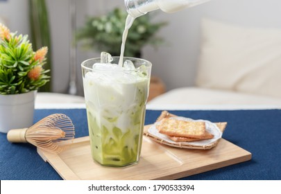 Green Tea Latte Iced, The Hands of Brewers Pour Fresh Milk Into a glass of green tea