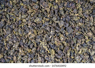 Green tea leaves background. Oolong tea. Abstract food textures. Close up, top view