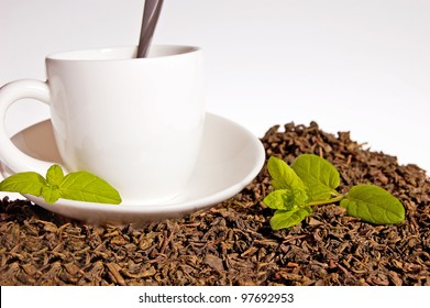 Green tea leaves and a cup of brewed tea with mint leaves