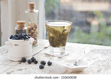 Green tea leaves in a glass in front of the window, still life blueberries in a white clay bucket