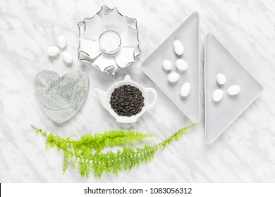 Green tea leaves, white chocolate and home decor styling. Flat lay composition on marble background.
