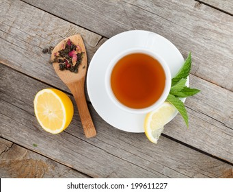 Green tea with lemon and mint on wooden table. View from above