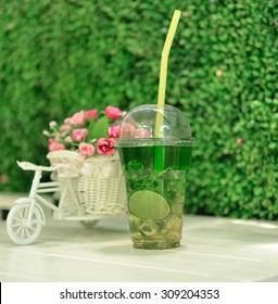 Green tea with lemon on background.