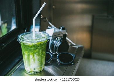 Green tea matcha atte in plastic cup with camera and glasses by the windiw in cafe.