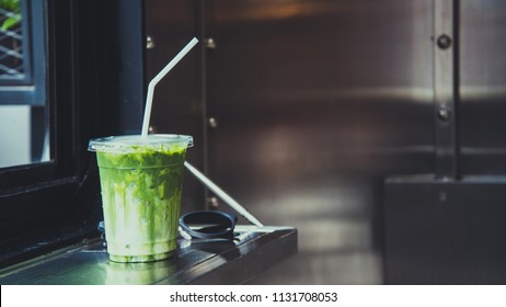 Green tea matcha atte in plastic cup with glasses by the windiw in cafe.