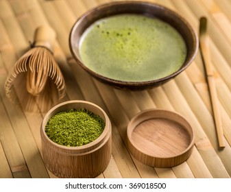 Green tea matcha in a bowl with whisk and spoon