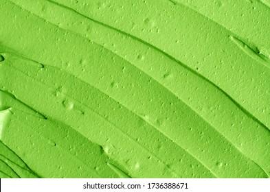 Green tea matcha facial mask (avocado face cream, body wrap) texture close up, selective focus. Abstract background with brush strokes.