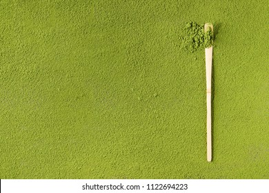 Green tea matcha powder in traditional bamboo spoon over powdering matcha as background.