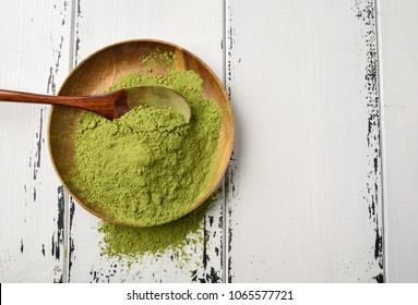 Green tea matcha powder in a wooden bowl and wooden spoon