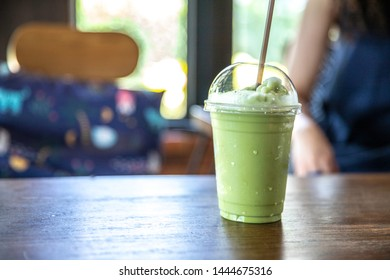 Green tea matcha smoothies in a plastic cup on wood table coffee shop.
