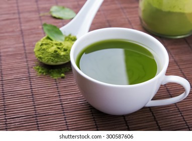 Green tea matcha in a white cup on the brown mat close-up