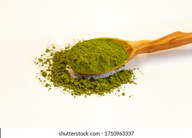 Green tea matcha in a wooden spoon on a white background close-up. Dry green tea. Macro of a match. Side view.