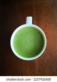 Green tea with milk or hot matcha latte in a cup on the wooden table in cafe with copy space