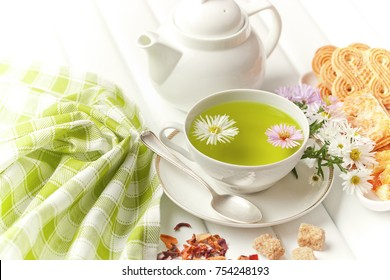 Green tea in a mug in a composition with leaves and flowers on a white background