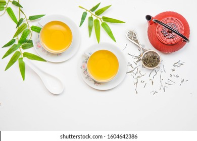 Green tea on White Asian Food Background with red teapot, cups and bamboo branches