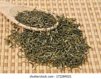 Green tea on a wooden spoon. Type is spring bud green tea