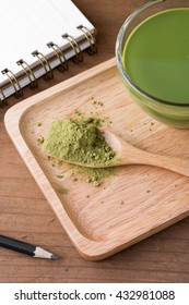 Green tea powder on wooden spoon and cup with note book and pencil on wooden table