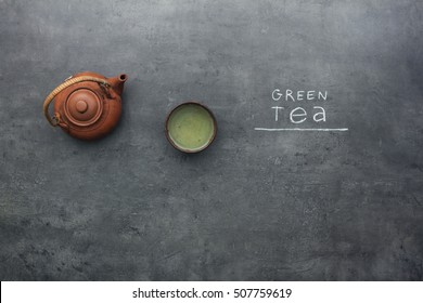 Green tea preparation process on kitchen table with chalky text instructions. Top view on teapot and tea accessories.