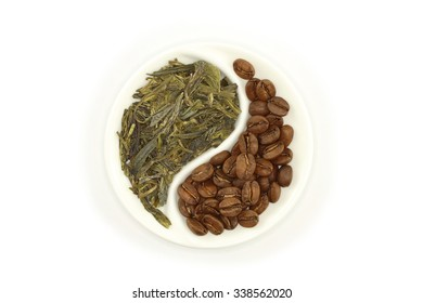 Green tea and roasted coffee beans in round Yin and Yang saucer on white background