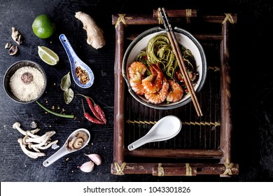 Green tea soba noodles  served with shrimps, shiitake and spicy broth on a vintage bamboo tray.  Decorated with different spices used during preparation: garlic, lime, chili pepper, shimeji