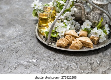 Green tea and traditional sweets baklava. Oriental silver tableware. Selective focus