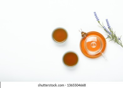 Green tea in a transparent teapot and small cups on a white table. Useful natural diet drink. Copy space, top view, flat lay.
