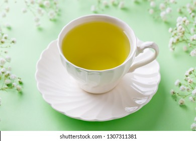 Green tea in a white cup with gypsophila flowers on green pastel background. Close up.