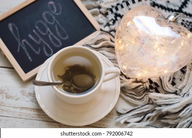 "Green tea in white cup, heart shaped lantern, knitted blanket and blackboard with word ""hygge"". Hygge concept. Comfort and coziness at home"