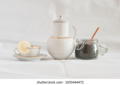 Green tea in a white cup, a slice of lemon on a saucer and a teapot on a white background.
