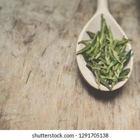 Green tea in wooden spoon/toned photo