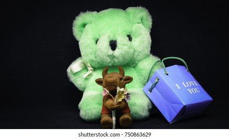 "Green teddy bear toy with blue bag labeled ""I love you"" and ox small toy with a bouquet of flowers on black background"