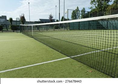 green tennis court in the town of la spezia