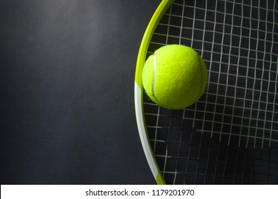 green tennis racket with  tennis balls in green color, isolated on black background, lighting detail sport concept