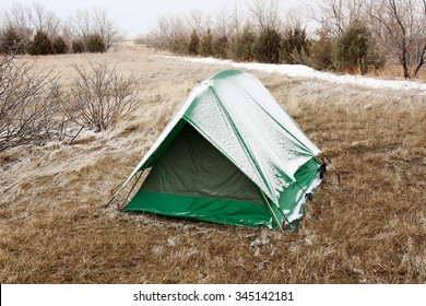 A green tent covered in snow on a cold winter's day.